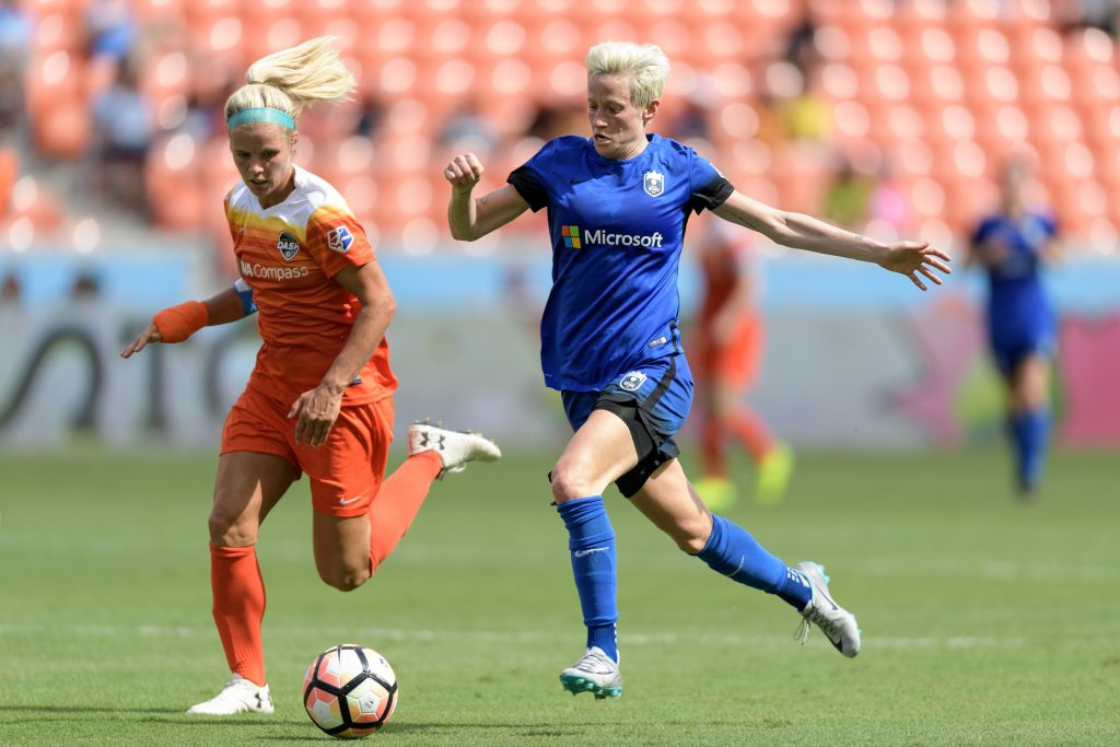 Seattle Reign midfielder/winger Megan Rapinoe and another soccer player chasing a ball