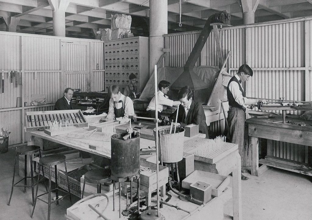 Old black and white photo shows workers manufacturing products by hand