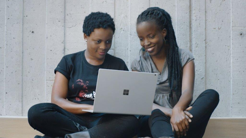 Two women sit together, looking at a laptop screen.
