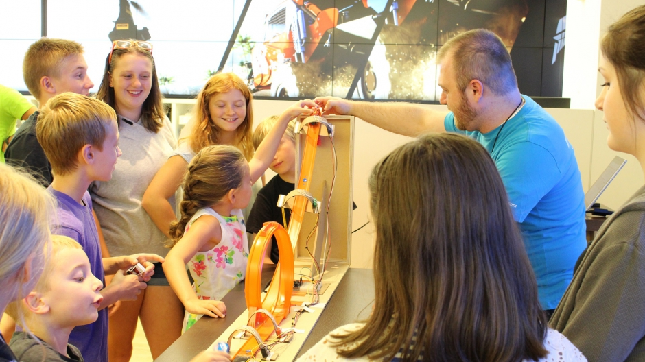 A group of children watch a demonstration of the Hot Wheels orange track game.
