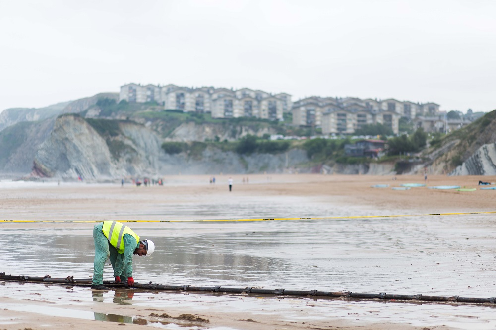 Man in hard hat adjusts cable on a sandy beach