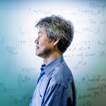 Photo of Peter Lee standing in front of a whiteboard covered in writing