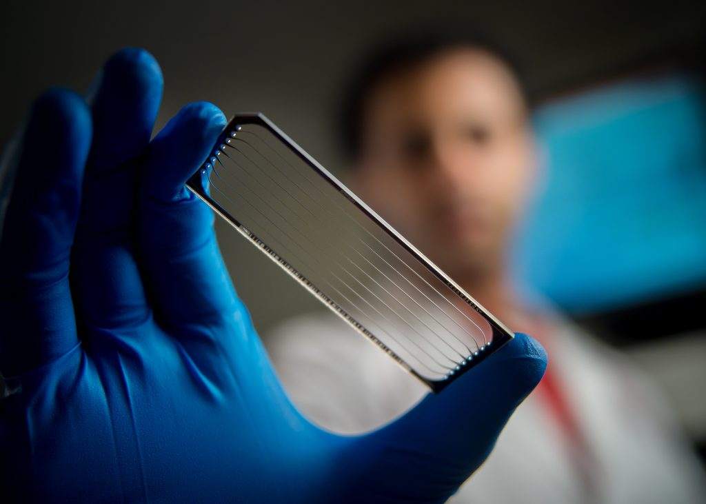 A scientist holds a flow cell used for genomic sequencing of pediatric cancers