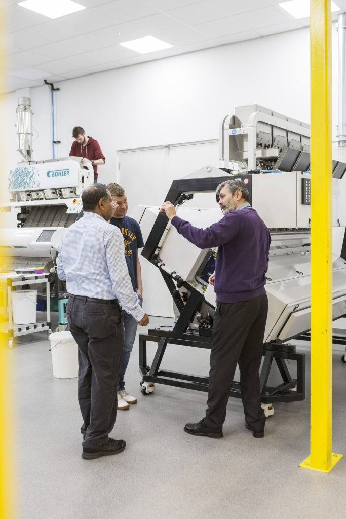 Photo shows man demonstrating how a machine taller than he is works
