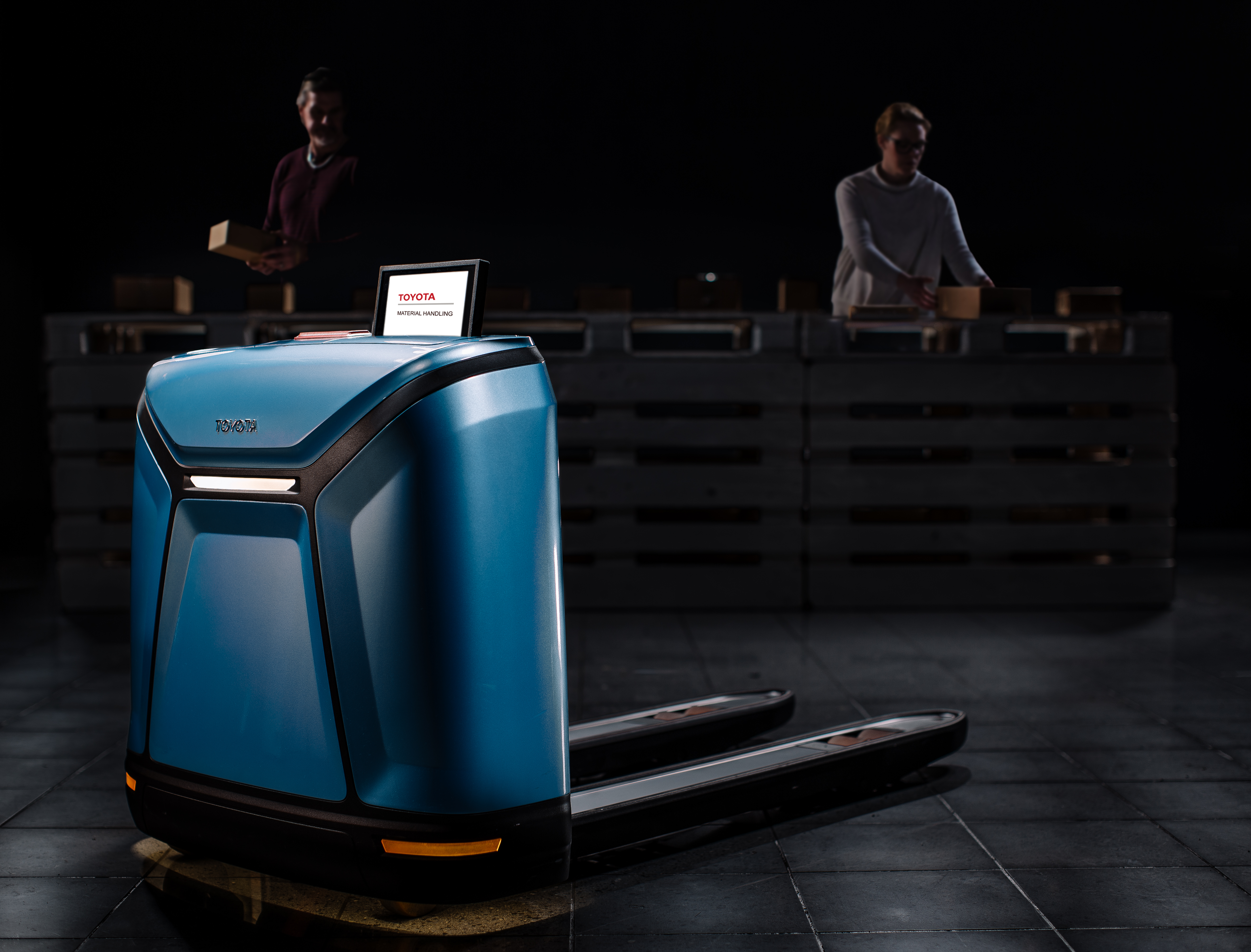 Photo of a sleek blue drone with arms similar to that of a fork lift, and two people working at a conveyor belt in the background