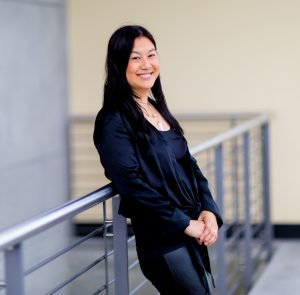 Photo of Lili Cheng leaning against railing inside a modern office building and smiling