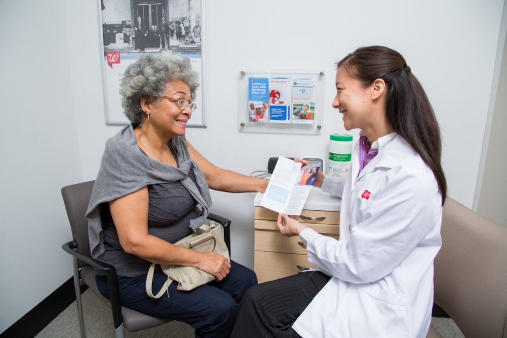 Pharmacy staff member with patient