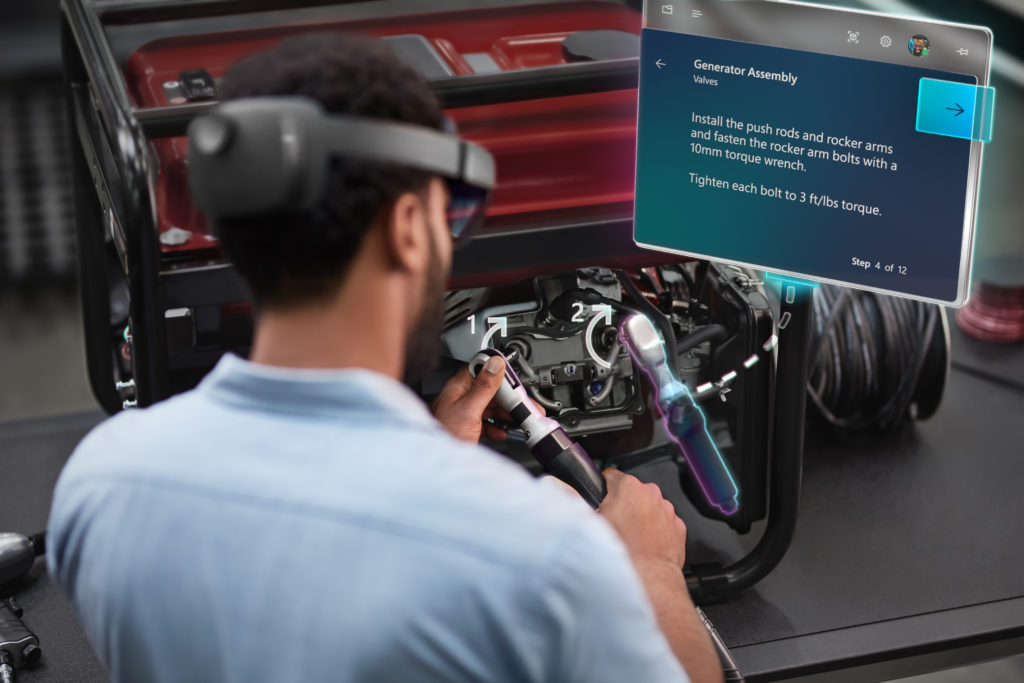 Man wearing HoloLens 2 consults a hologram of a guide as he works on machinery
