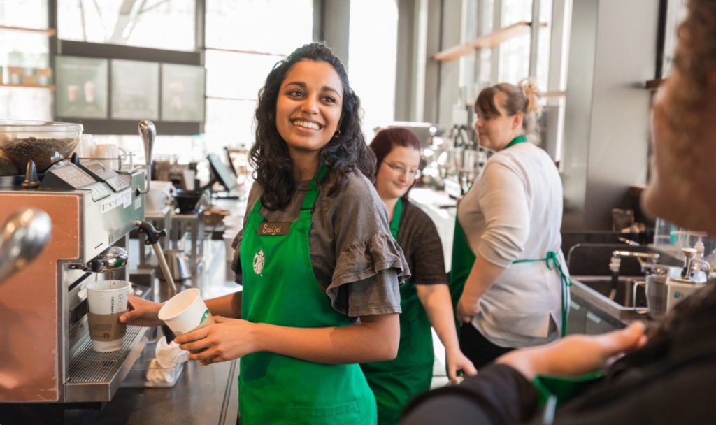 Photo of Starbucks barista smiling and making an espresso drink