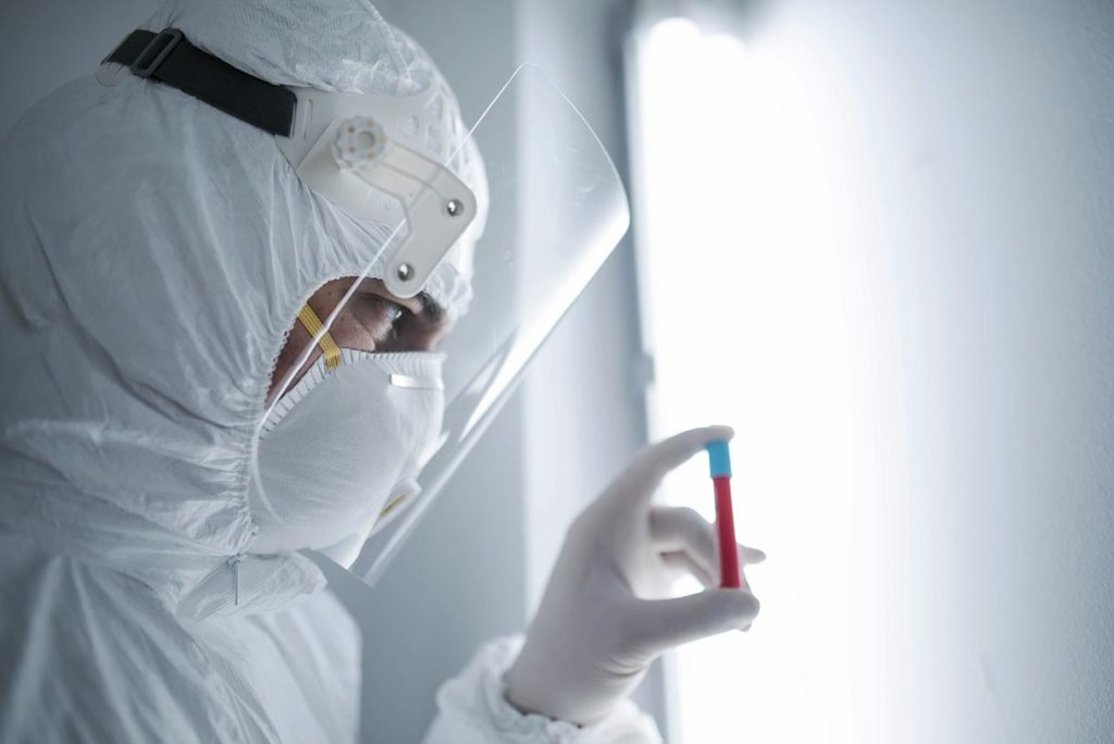 Lab technician with vial of blood