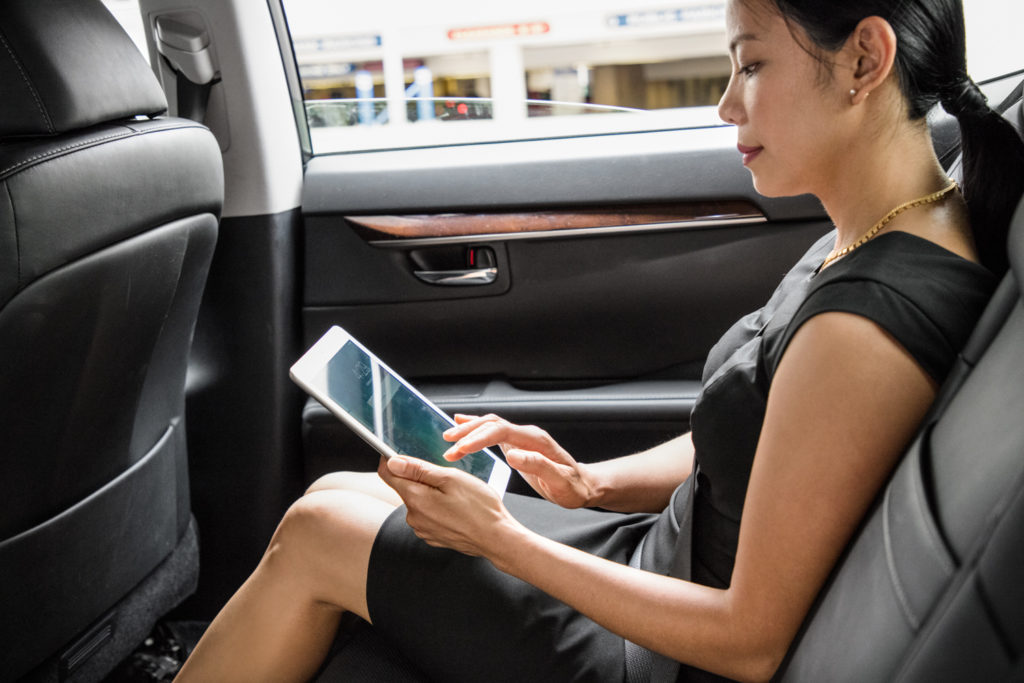 Woman interacts with a tablet computer while sitting in a car